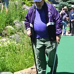 Fr. Tony is a two-fisted golfer: cane in one hand and putter in the other