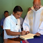 Paul signs the house journal while Fr. Byron looks on